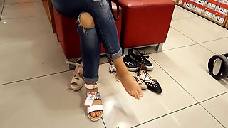 Young fr dangling sexy feets at shoe shopping