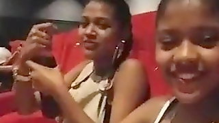 Two black girls doing at a cinema
